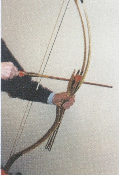 Detail of the string nock and the hand holding bow with arrows in position.